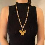 woman wearing a long atteza rose quartz necklace on black turtleneck