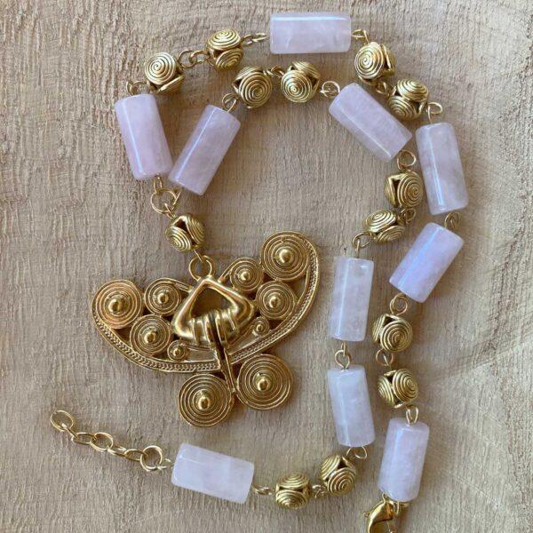 mariposa rose quartz necklace lying over a wooden slab